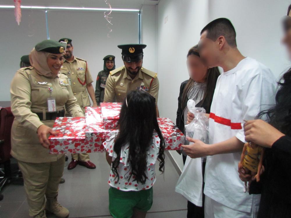 ابنة النزيل أثناء تسلمها هدايا عيد ميلادها بحضور والديها من إدارة السجن في دبي. (الرؤية)