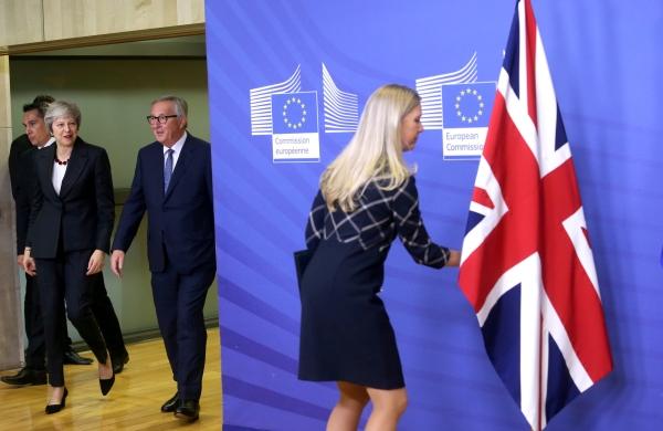 موظفة تعدّل وضع العلم البريطاني قبيل حضور ماي ويونكر مؤتمراً صحافياً في بروكسل. (رويترز)
