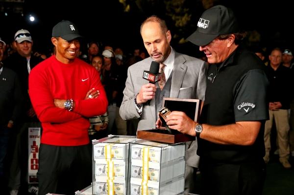 نجم الغولف الأمريكي فيل ميكلسون يتسلم جائزة الفوز على تايغر وودز، أمس الأول. (أ ف ب)
