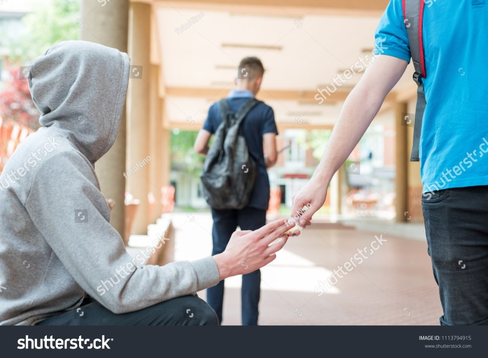 stock-photo-highschool-student-buying-drugs-from-local-dealer-on-school-grounds-in-front-of-other-minor-1113794915