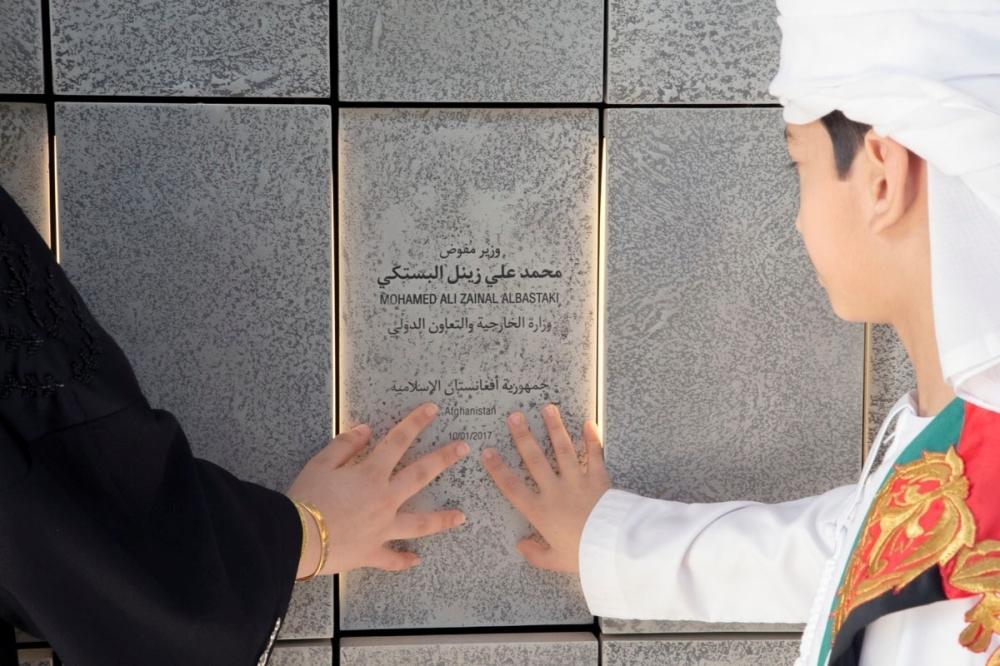 ابنا الشهيد محمد البستكي أثناء اطلاعهما على اسم والدهما في جدار واحة الكرامة بأبوظبي. (الرؤية)