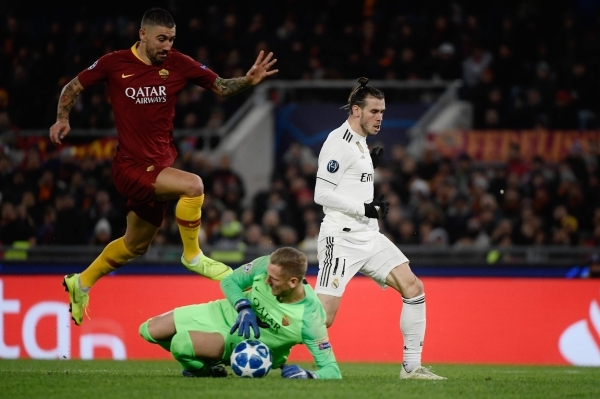 AS Roma Swedish goalkeeper Robin Olsen (C) saves a ball under pressure form Real Madrid's Welsh forward Gareth Bale (R) as AS Roma Serbian defender Aleksandar Kolarov jumps over him during the UEFA Champions League group G football match AS Rome vs Real Madrid on November 27, 2018 at the Olympic stadium in Rome. (Photo by Filippo MONTEFORTE / AFP)