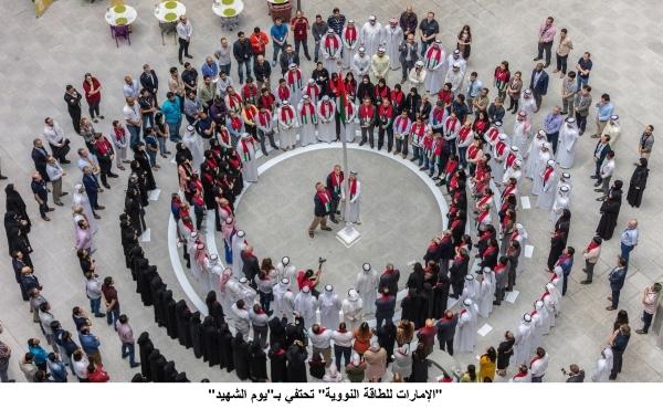 مسؤولو وموظفو «الإمارات للطاقة النووية» والشركات التابعة ملتفين حول سارية علم الدولة في أبوظبي أمس. (وام)