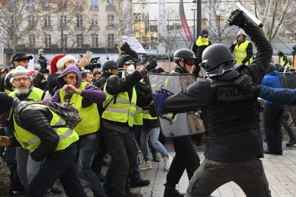 """Riot police clash with men wearing """"yellow vests"""" (gilets jaunes) protestors on December 8, 2018 near the Arc de Triomphe in Paris during a protest against rising costs of living they blame on high taxes. - Paris was on high alert on December 8 with major security measures in place ahead of fresh """"yellow vest"""" protests which authorities fear could turn violent for a second weekend in a row. (Photo by Alain JOCARD / AFP)"""