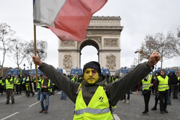 """A man wearing a """"yellow vest"""" (gilet jaune) holds a French flag on the Champs Elysees avenue on December 8, 2018 in Paris during a protest against rising costs of living they blame on high taxes. - Paris was on high alert on December 8 with major security measures in place ahead of fresh """"yellow vest"""" protests which authorities fear could turn violent for a second weekend in a row. (Photo by Eric FEFERBERG / AFP)"""