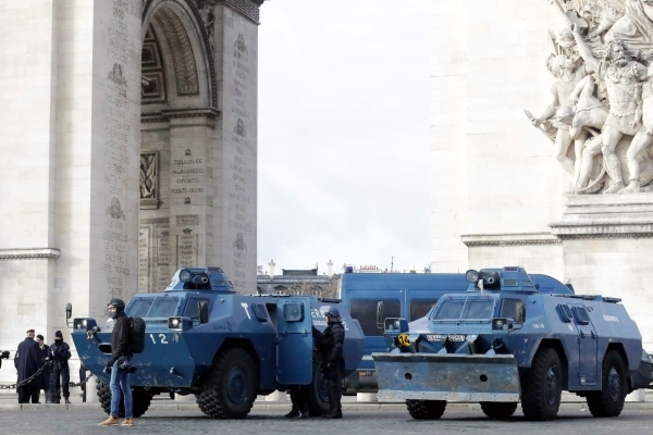 """A protestor stands next to gendarmerie armored vehicles (VBRG) parked near the Arc de Triomphe in Paris on December 8, 2018 during a """"yellow vests"""" (gilets jaunes) mobilisation protesting against rising costs of living they blame on high taxes. - Paris was on high alert on December 8 with major security measures in place ahead of fresh """"yellow vest"""" protests which authorities fear could turn violent for a second weekend in a row. (Photo by Thomas SAMSON / AFP)"""