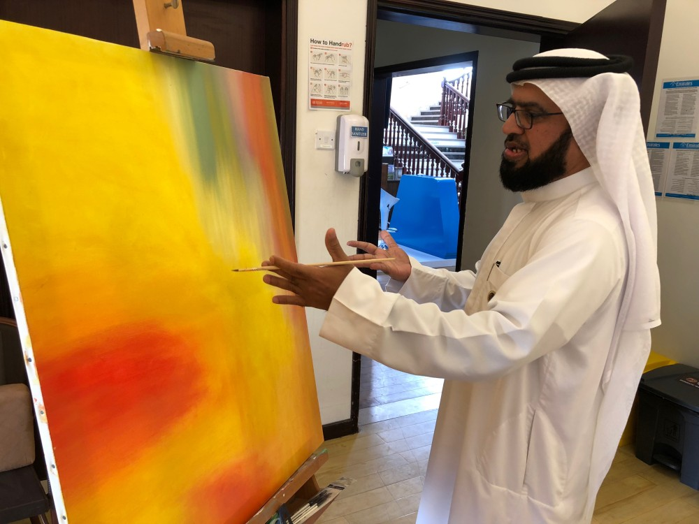 علي الأميري أثناء إنجازه إحدى لوحاته الحروفية. (الرؤية)