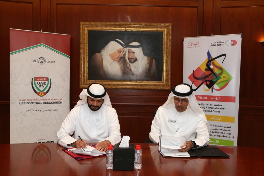 مروان بن غليطة وطارش المنصوري يوقعان اتفاقية بين اتحاد الكرة ومحاكم دبي أمس. (الرؤية)