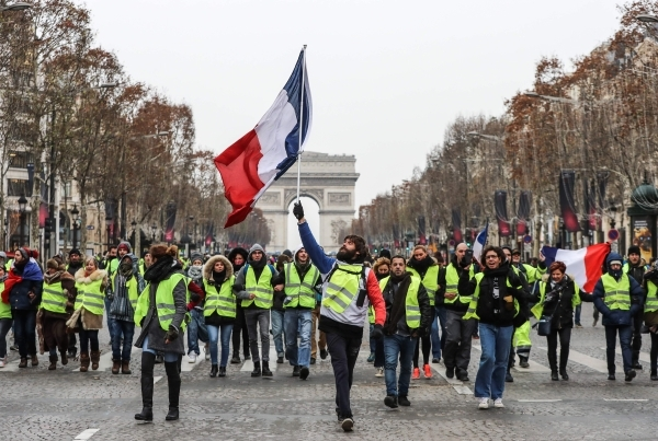 TOPSHOT - A protester wearing a yellow vest (gilet jaune) waves the French national flag during a demonstration against rising costs of living blamed on high taxes on the Champs-Elysees in Paris, on December 15, 2018. - The