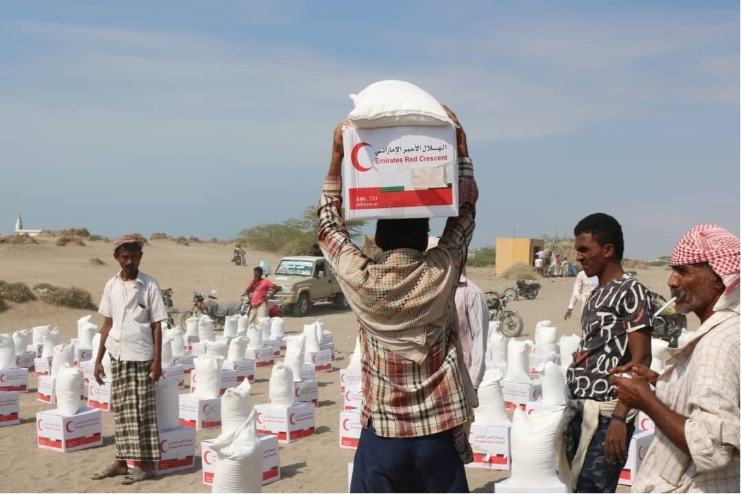 يمنيون يتلقون المساعدات الإماراتية في الساحل الغربي. (وام)