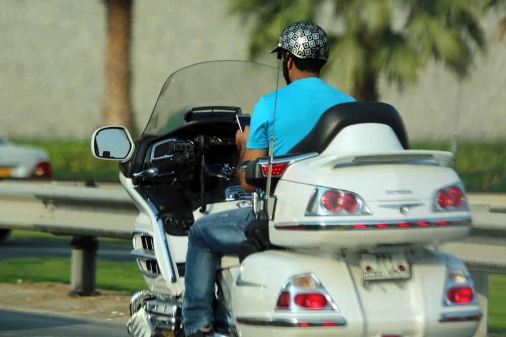 A man checks his phone while on his motorcycle at Ittihad Road, Dubai, UAE on 21 November 2016.