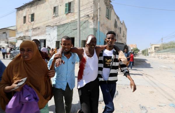 صوماليون يحملون جريحاً أصيب في الهجوم الإرهابي وسط مقديشو أمس. (رويترز)