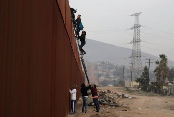 مهاجرون يتسلقون السياج الحدودي بين المسكيك وأمريكا. (رويترز)