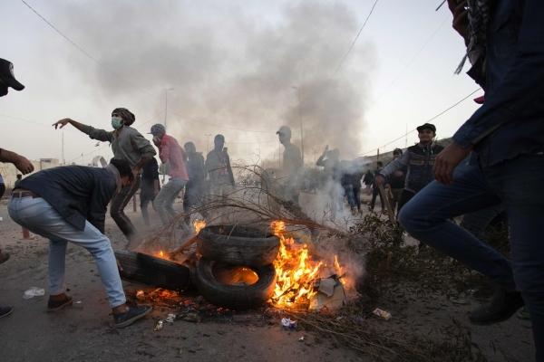 متظاهرون في البصرة يحرقون إطارات السيارات لقطع الطرق أمام الأجهزة الأمنية. (أ ف ب)