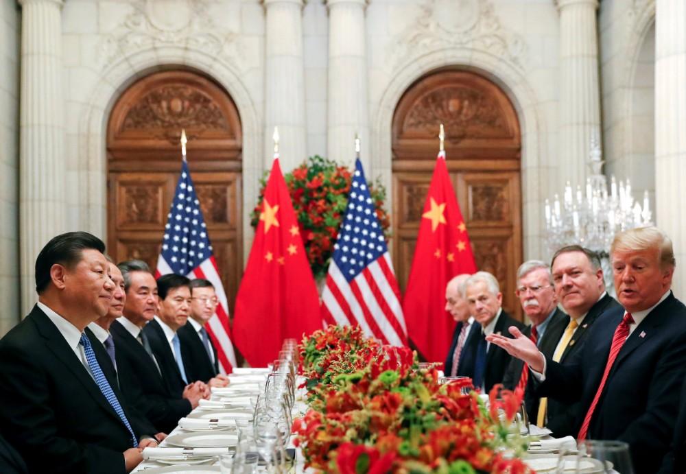 صيني يلتقط صوراً لمبنى وزارة التجارة في بكين أمس حيث يجتمع الوفد الأمريكي مع نظيره الصيني لمدة يومين من المحادثات التجارية بين البلدين. (إي بي إيه)