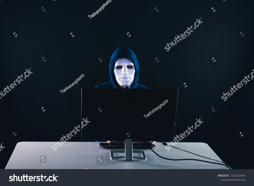 stock-photo-anonymous-and-masked-hacker-under-hoodie-using-computer-isolated-over-dark-background-illegal-1150253594
