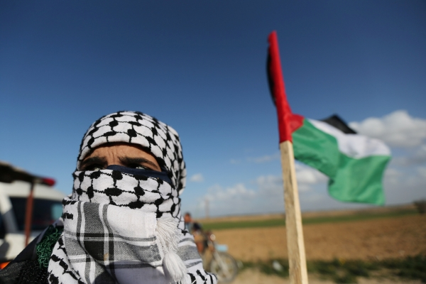 متظاهر فلسطيني بالقرب من السياج الحدودي في غزة. (رويترز)