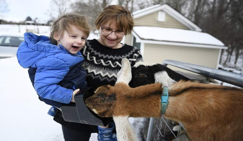 """This March 6, 2019 handout photograph, obtained March 8, 2019 courtesy of the Rutland Herald, shows Sally Stanton (R) holding her grandson Murphy Drzewianowski as he feeds Lincoln the goat, who was elected """"Pet Mayor"""" for the town of Fair Haven, Vermont. - During votes cast in the community's March 7, 2019 Town Meeting Day, Lincoln became the first one-year honorary """"Pet Mayor"""" of Fair Haven, a small town in the northeastern US state of Vermont. The ballot of 16 pets was open to all residents of the town, which does not have a human mayor. While mayor, Lincoln will be attending local events that will include marching in the Memorial Day parade. (Photo by Robert LAYMAN / Rutland Herald / AFP) / == RESTRICTED TO EDITORIAL USE / MANDATORY CREDIT: """"AFP PHOTO / RUTLAND HERALD / Robert LAYMAN"""" / NO MARKETING / NO ADVERTISING CAMPAIGNS / DISTRIBUTED AS A SERVICE TO CLIENTS =="""