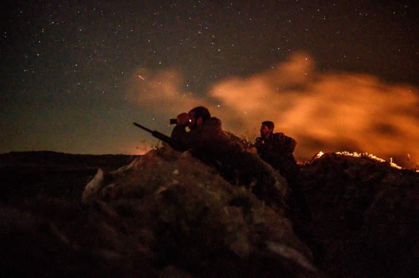 مقاتلان من قسد يراقبان تحركات عناصر داعش في الباغوز. (أ ف ب)