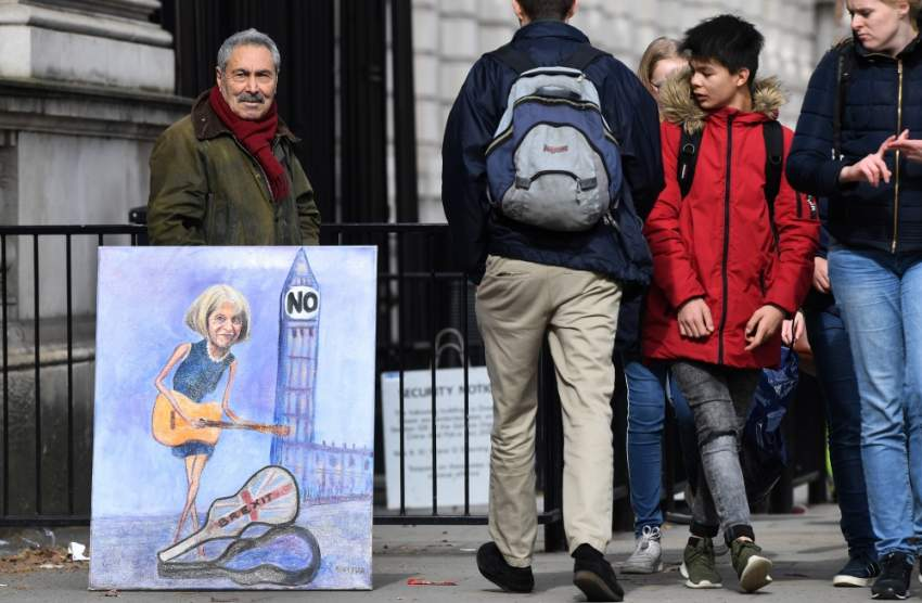 الفنان الساخر كايا مار مع لوحة تعبر عن رفض «بريكسيت» في لندن. (إي بي إيه)