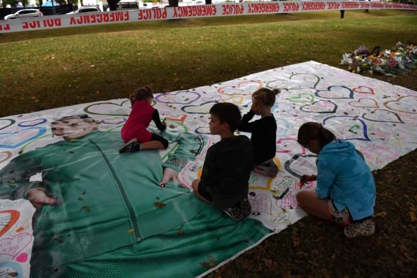 أطفال يرسمون قلوباً على لوحة تذكارية أمام مسجد النور