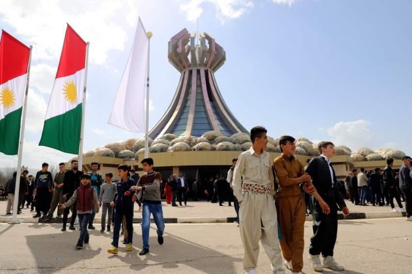أكراد عراقيون عند النصب التذكاري لضحايا حلبجة. (أ ف ب)