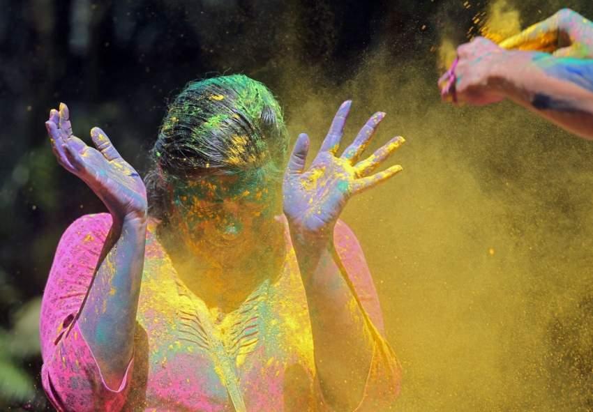 فتاة تحاول تجنب الألوان في مومباي خلال الاحتفال بـهولي