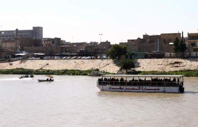 عراقيون يستقلون عبارة وسط نهر دجلة. (إي بي إيه)