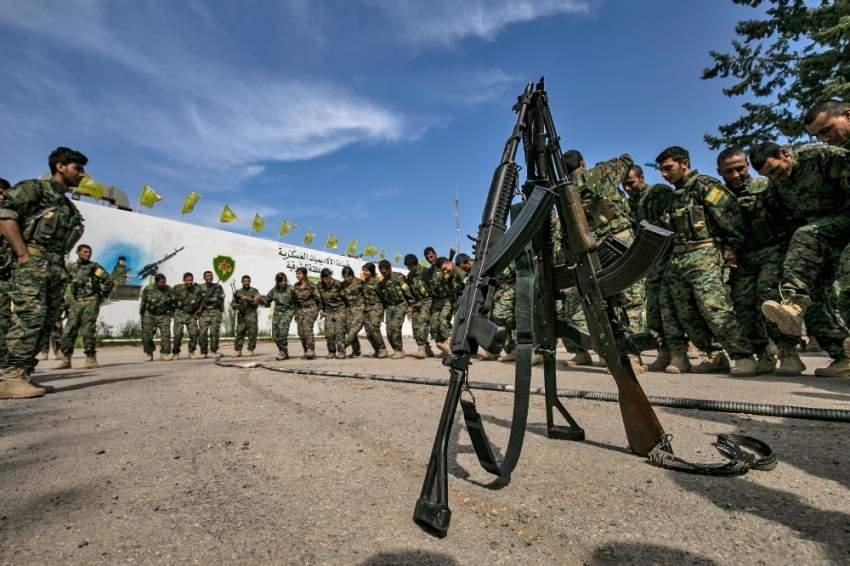 مقاتلون أكراد يحتفلون بالقضاء على فلول داعش في الباغوز. (أ ف ب)