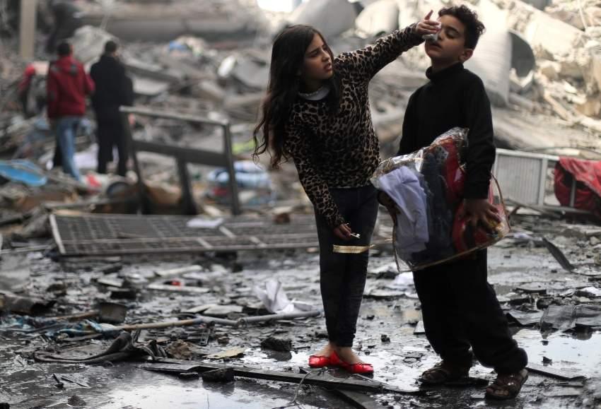 طفلة فلسطينية تتفقد وجه شقيقها المصاب بعد تدمير منزلهما في غارة إسرائيلية على غزة. (رويترز)