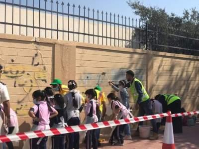 طلبة المدارس في العين ينظفون الجدران ضمن مبادرة الشرطة. (الرؤية)