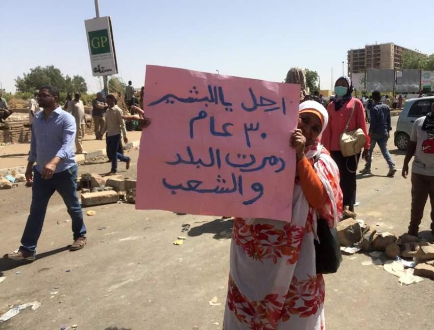 سودانية أمام مقر القيادة العامة للجيش تحمل لافتة تطلب البشير بالتنحي. (أ ف ب)