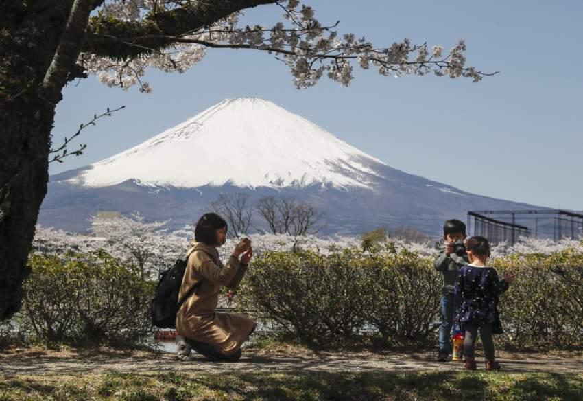 امراة تلتقط صورة تذكارية لأبنائها ويظهر جبل فوجي أكبر قمة في اليابان