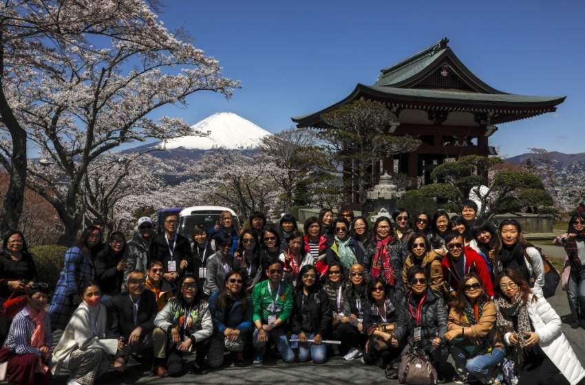 مجموعة من السواح اليابانيين يلتقطون صورا تذكارية ويظهر خلفهم أعلى قمة جبل في اليابان