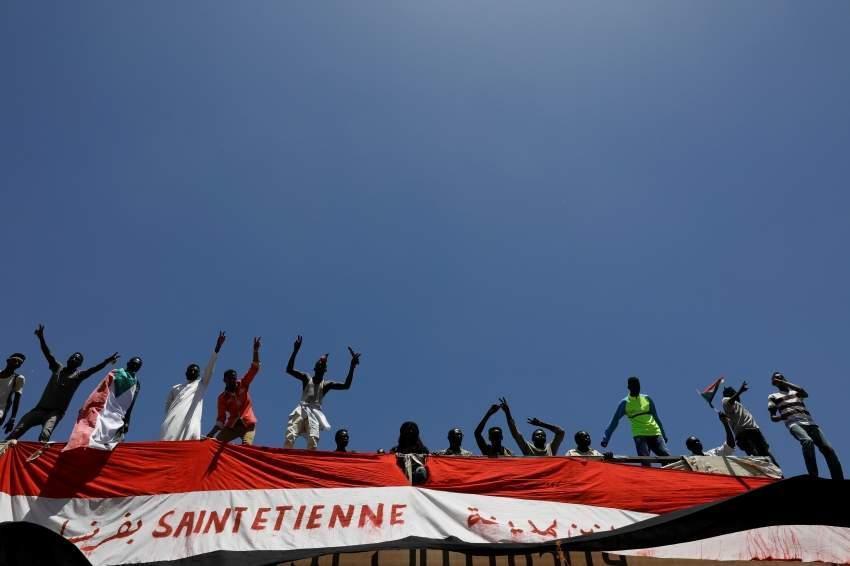 متظاهرون سودانيون يقفون على جسر بالقرب من مقر وزارة الدفاع. (رويترز)