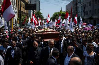 People carry the coffin with the remains of late Peruvian ex-president Alan Garcia during his funeral procession in Lima, on April 19, 2019. - Garcia, who was president from 1985-90 and again from 2006-11, died in hospital on Wednesday after shooting himself in the head at his home as police were about to arrest him over the graft investigation. He was suspected of having taken bribes from Brazilian construction giant Odebrecht in return for large-scale public works contracts. (Photo by ERNESTO BENAVIDES / AFP)
