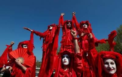 نشطاء البيئة يرتدون الملابس الحمراء فوق جسر واترلو في لندن امس (رويترز)