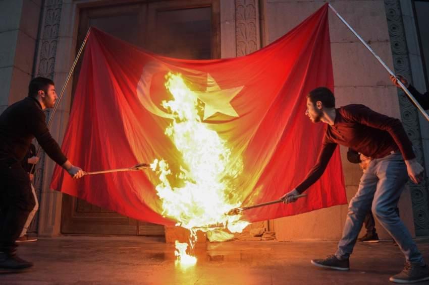 شابان يحرقان العلم التركي في العاصمة الأرمنية خلال ذكرى الإبادة. (أ ف ب)