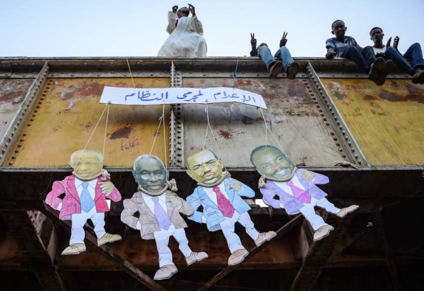 دمى تجسد الرئيس السوداني السابق ورموز نظامه. (أ ف ب)