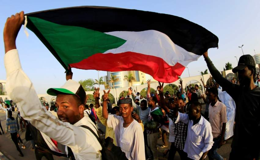Sudanese protesters carry their national flag as they chant slogans before breaking their fast during the first day of the fasting month of Ramadan, in front of the Defence Ministry compound in Khartoum, Sudan May 6, 2019. REUTERS/Mohamed Nureldin Abdallah