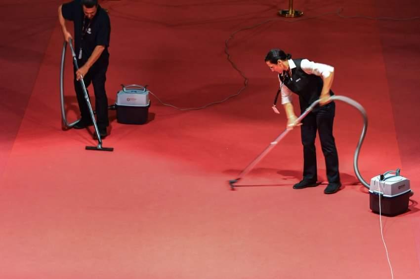 عاملي النظافة يقومون يتنظيف السجادة الحمراء بعد وصول ضيوف المهرجان