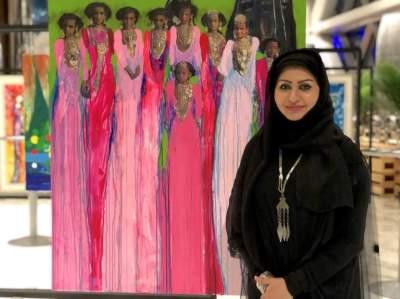 خلود الجابري وإحدى لوحاتها في معرضها الفني بأبوظبي.