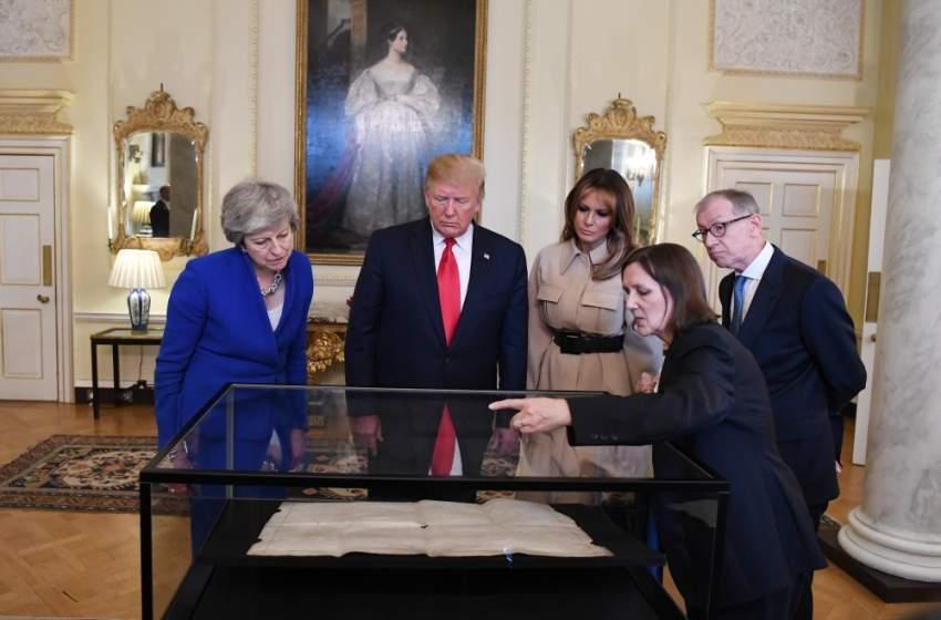 ترامب وزوجته يتفحصان مع ماي وزوجها وثيقة تاريخية. (إي بي أيه)