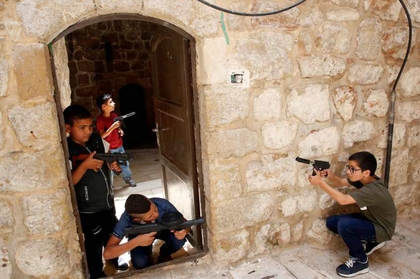 أطفال فلسطينيون يلعبون في الخليل ببنادق مزيفة. (أ ف ب)