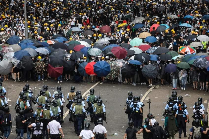 المحتجون واجهوا خراطيم شرطة هونغ كونغ المياه بالمظلات أ ف ب