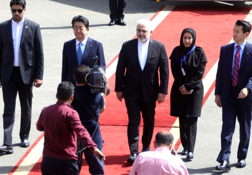 شينزو آبي لدى وصوله إلى طهران وفي استقباله وزير الخارجية الإيراني. (أ ف ب)