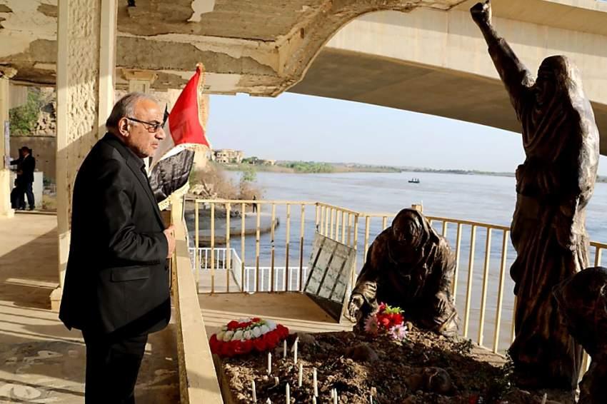 رئيس الوزراء العراقي لدى زيارته نصباً تذكارياً لضحايا داعش. (أ ف ب)