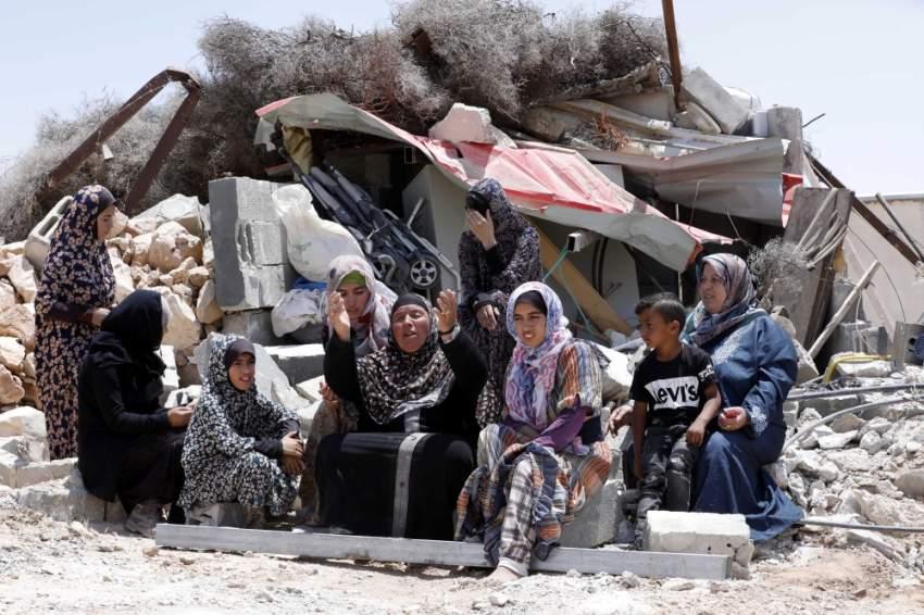 أسرة فلسطينية على أنقاض منزل دمرته قوات الاحتلال الإسرائيلي في الخليل. (إي بي إيه)