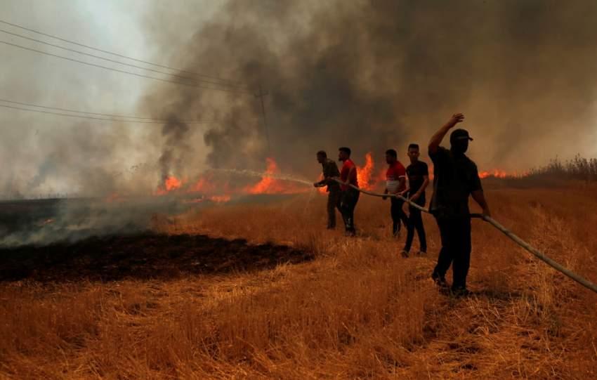 عراقيون يحاولون إطفاء حريق في حقل قمح قرب الموصل. (رويترز)