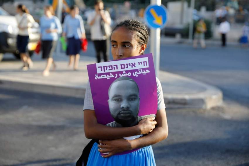 فتاة تحمل صورة الشاب سلمان تيكاه الذي اثار مقتله الاحتجاجات. أ ف ب